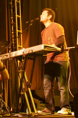 Keyboard player singing into a microphone, playing on stage