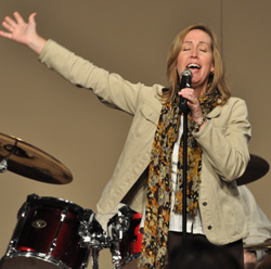 Female singing into a microphone, eyes, closed, one hand up in the air