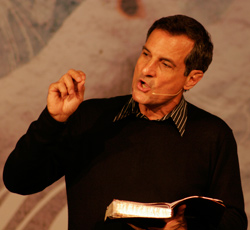 Pastor preaching with bible in one hand, wearing a headworn microphone
