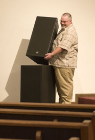 Man stacking speakers in a church setting