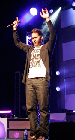 Man holding a microphone on stage with hands held up to the sky