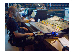 Church sund technicians sitting at the back of large worship space in front of large audio mixing boards