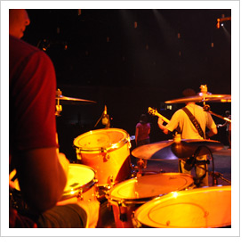 drummer sitting at a drum set on stage behind a singer