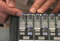 Man's hands adjusting Trim control on a mixing board