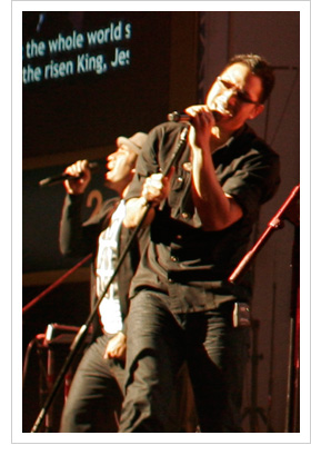 Two worship leaders singing on stage