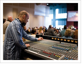 Church Sound Technician working in front of a large audio mixing console
