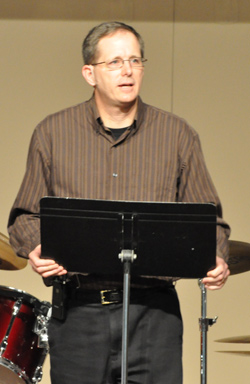 Male Pastor preaching from a music stand wearing a tiny ear worn mic