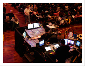 Overhead view of sound boards, computers and various tech gear and tech guys in front of church