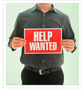 Man holding a Help Wanted Sign