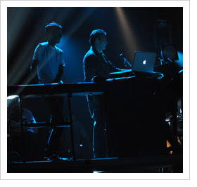 Worship team at keyboards and laptop performing under blue spotlights