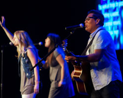 Worship leader with an acustic guitar singing into a microphone
