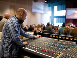 Church tech guy leaning over the short wall by front of house sound mixing station